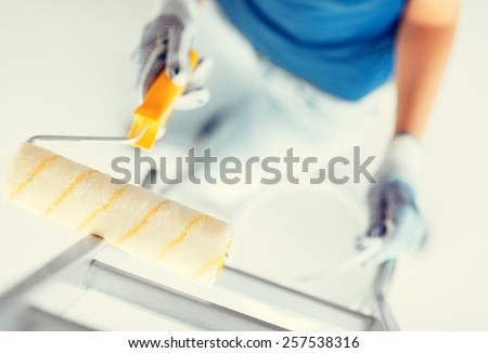 interior design and home renovation concept - woman with roller and paint pot - stock photo