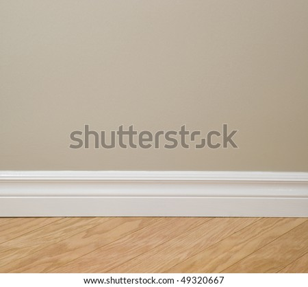 Interior design detail. Beige wall, clean white baseboard molding and wooden floor. - stock photo