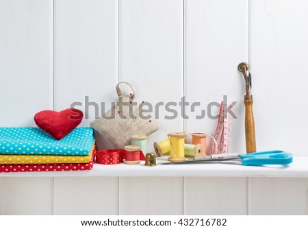 Interior design for seamstress. Set of reel of thread, centimeter, fabric, thimble and scissors, seam ripper, toothed wheel, needle and pins for sewing and needlework on the wooden shelf   - stock photo