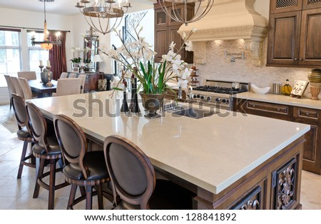 Interior design of a luxury modern kitchen with a dining set behind. - stock photo