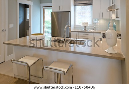 Interior design of a luxury modern kitchen with two sits and the dish with some pears on the counter. I - stock photo