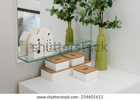 Interior design of a modern bedroom with green vase and decoration boxes on dressing table - stock photo