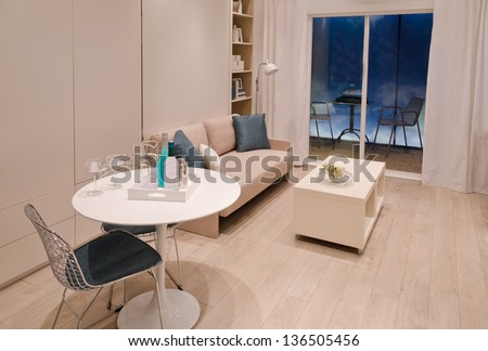 Interior design of a modern living room with a table, sofa and a coffee table - stock photo