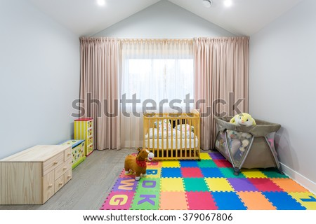 Interior design of a nursery room with a crib and toys.  - stock photo