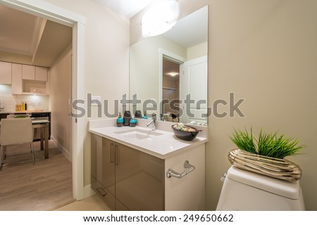 Interior design of a spacious and elegant bathroom with a dining room in the background. - stock photo