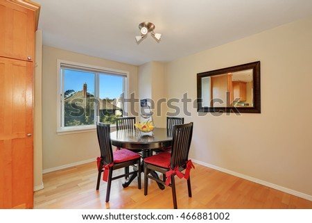 Interior design of dining room. Black table and chair set, vintage mirror on the wall and wood flooring. Northwest, USA