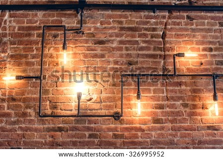 interior design of vintage wall. Rustic design, brick wall with light bulbs and pipes, low lit bar interior - stock photo