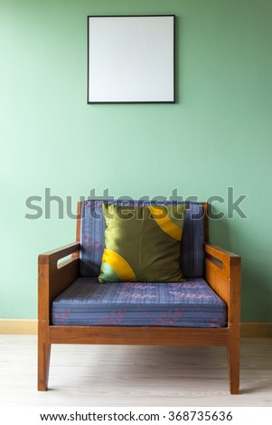 Interior design with Wooden armchair on wooden floor with green background and  decoration by picture frame