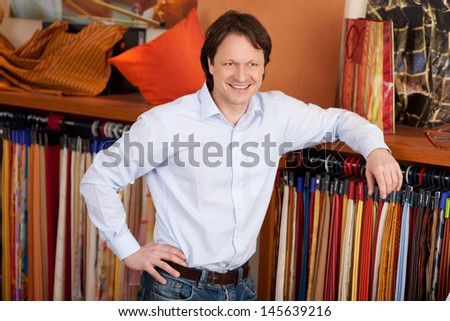 Interior designer in his studio leaning nonchalantly on a row of hanging fabric samples with a confident smile - stock photo