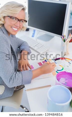 Interior designer looking up from her work at desk with colour wheel and paint pots - stock photo
