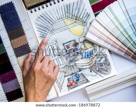 Interior designer's  hand working with illustration sketch,  material and color samples
