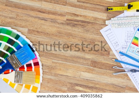 Interior designer's working desktop with  architectural plan of the house, color palette and  brushes, copy space on wooden table - stock photo