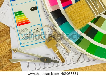 Interior designer's working desktop with  energy rating chart, architectural plan of the house, color palette and  brushes - stock photo
