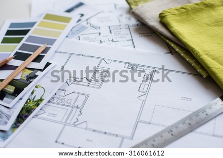Interior designer's working table, an architectural plan of the house, a color palette, furniture and fabric samples in yellow and grey color. Drawings and plans for house decoration. - stock photo