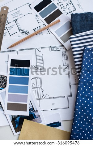 Interior designer's working table, an architectural plan of the house, a color palette, furniture and fabric samples in blue color. Drawings and plans for house decoration. - stock photo