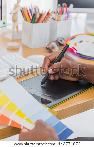 Interior designer with graphics tablet and colour chart in a modern office - stock photo