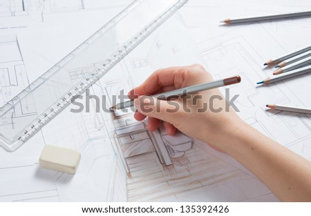 Interior designer works on a hand drawing sketch using color pencils, rule and rubber - stock photo