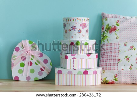 Interior detail. Home shelf with shabby chic gift boxes and pillow on it over blue wall - stock photo