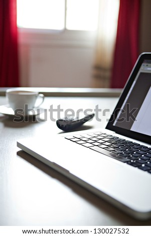 Interior detail view of a laptop computer on a home living room coffee table, with a telephone and a cup of coffee near a window with curtains. - stock photo