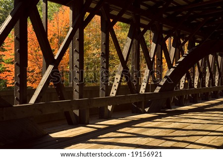 Interior details of a wooden covered bridge with the beautiful colors of the autumn trees as a background. - stock photo