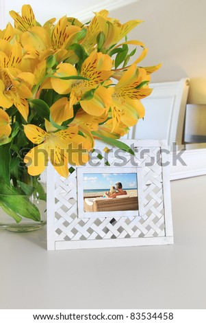 Interior framed picture and flowers in vase - stock photo