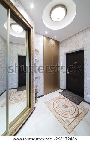 Interior hallway with entrance door and sliding mirror wardrobe - stock photo