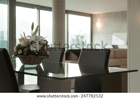 Interior home, modern dining table with basket of flowers