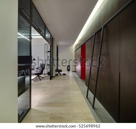 Interior in a modern style with light walls, glass partitions and partially concrete ceiling. There are wooden lockers and wardrobes, ladder, chair, armchair, TV, shelves with plants and decorations.
