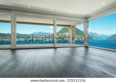 Interior, modern house, empty living room with windows overlooking the lake - stock photo