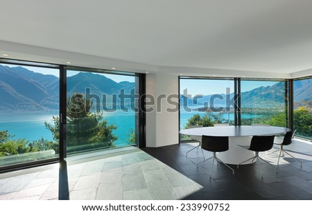 Interior, modern house, wide dining room with glass walls - stock photo