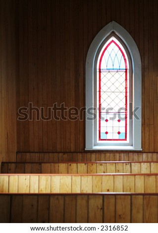 Interior of a church with pews and glass stained window