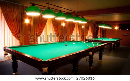 Interior of a club having billiard tables illuminated with lights