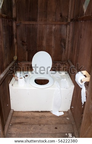 Interior of a dirty and disgusting outhouse with toilet paper littered around. - stock photo