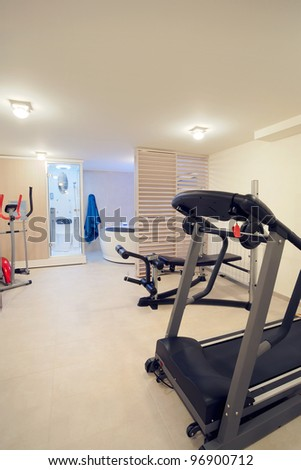 Interior of a fitness room with all necessary equipment, jacuzzi and toilet.