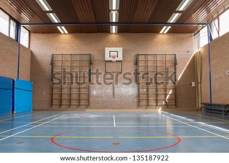 Interior of a gym at school, jumping high at the basket - stock photo