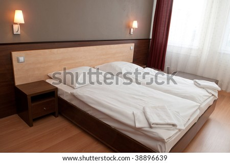 interior of a hotel room with double bed in the middle