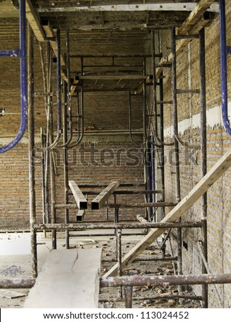 Interior of a house under construction with red brick walls and frameworks