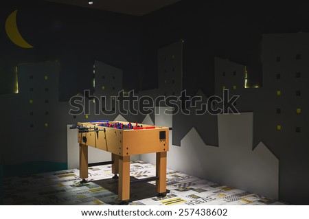 Interior of a kindergarten, details of a room with football table in the center.   - stock photo