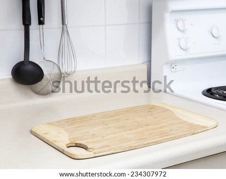 Interior of a kitchen, preparation for cooking: wooden cutting board, utensils, stove, background with copy space - stock photo