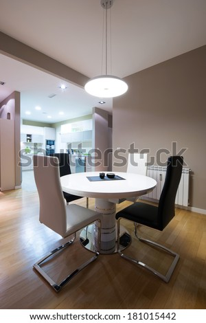 Interior of a luxury dining room with round table and a view to a kitchen