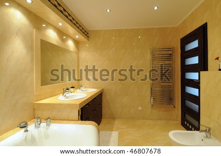 Interior of a modern bathroom with a mirror, lights and tub. - stock photo