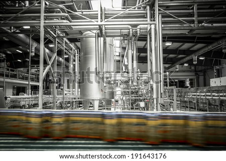 Interior of a modern brewery, beer cans on the conveyor belt - stock photo
