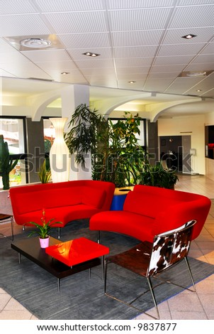 Interior of a modern european hotel lobby with red sofas - stock photo