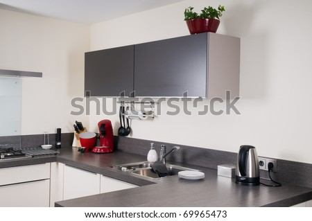 Interior of a modern grey and white kitchen with some kitchen attributes.