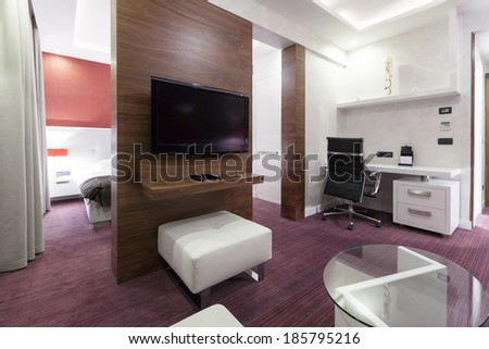 Interior of a modern hotel room with wall mounted tv in the evening - stock photo