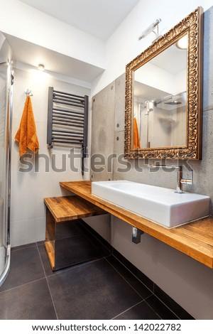 Interior of a new luxury bathroom with golden mirror - stock photo