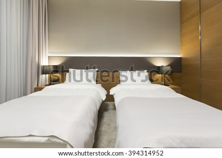 Interior of a new modern hotel bedroom in the evening