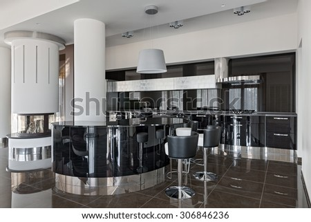 Interior of a new modern luxury kitchen with fireplace in daylight - stock photo