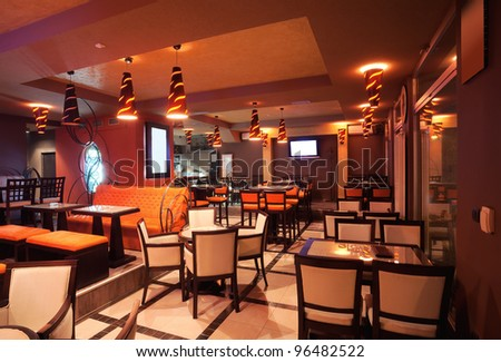 Interior of a restaurant, modern design in few colors, orange and brown. - stock photo