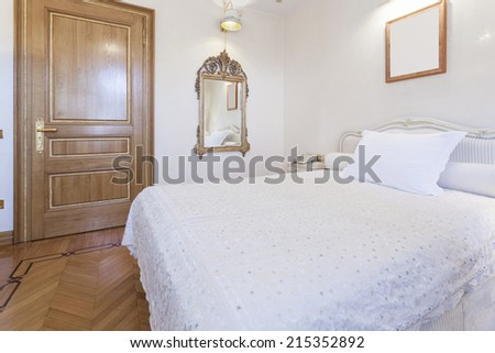 Interior of a small hotel room with antique mirror and empty picture frame - stock photo
